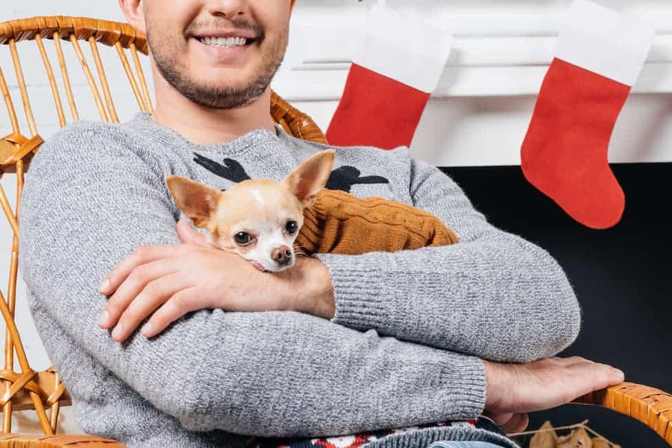 Mann hält Hund im Arm